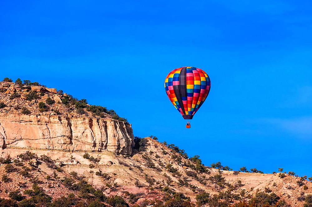 Hot air balloons flying during the Red Rock Balloon Rally, Red Rock State Park, near Gallup, New Mexico USA