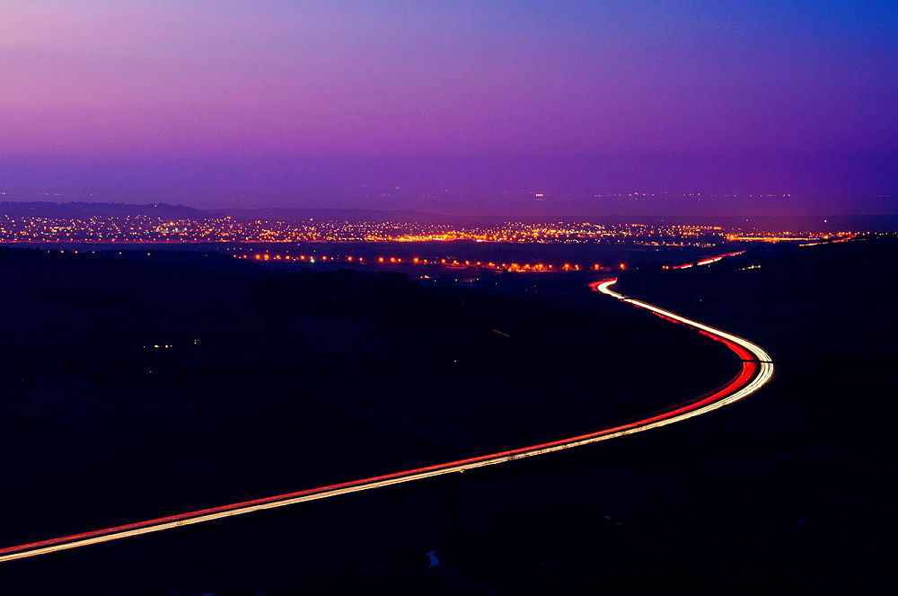 The M5 motorway and the lights of Weston-super-Mare viewed from Crook Peak on the Mendip Hills at dusk, Somerset, England