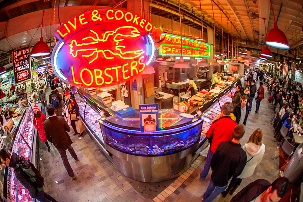 Shoppers at fish stall with lobster neon sign in the Reading Terminal Market in Philadelphia