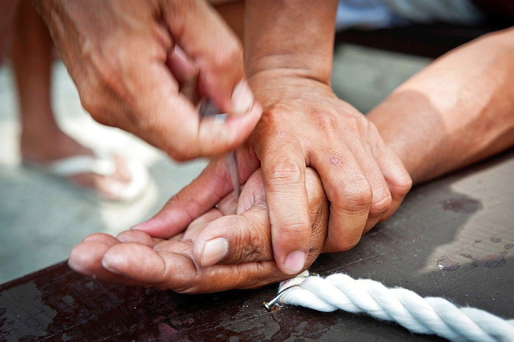 Detail of the hands of a crucified man while someone is removing the nails San Fernando, Pampanga, Philippines