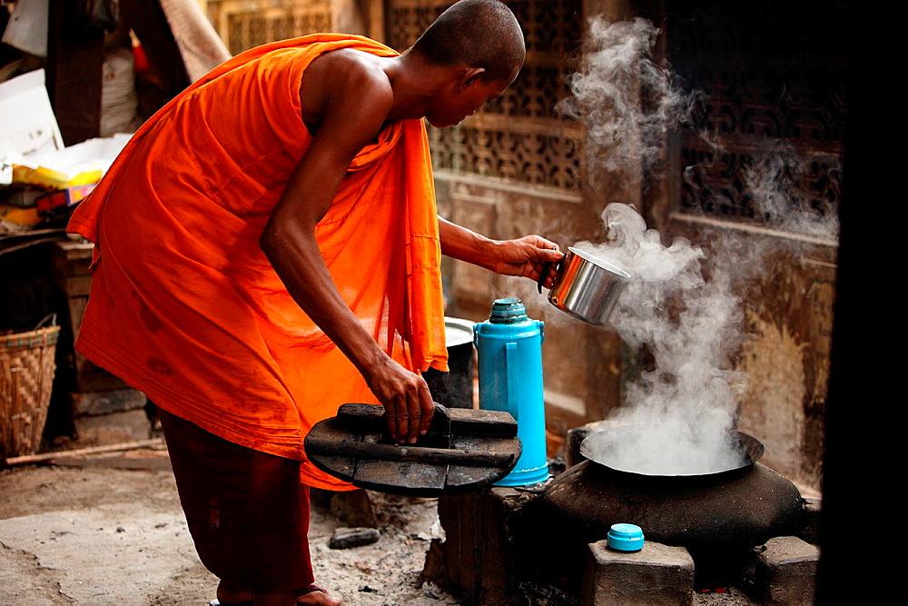 Monk at work boiling water, burman novice, Myanmar, Burma, Asia