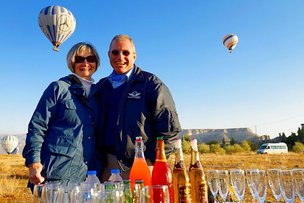 Hot air balloon pilot celebrating with female tourist a successful flight in Cappadocia Turkey
