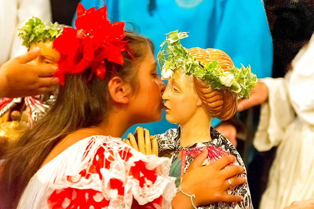 Europe, France, Bouche-du-Rhone, 13, Saintes-Marie-de-la-Mer, pilgrimage of gypsies  Young girl kissing the saints