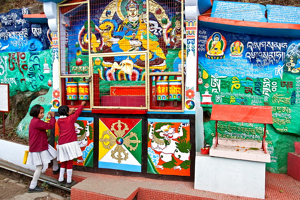 A Schoolgirl spins the prayer wheels of a Buddhist Shrine on her way to school, Darjeeling, West Bengal, India
