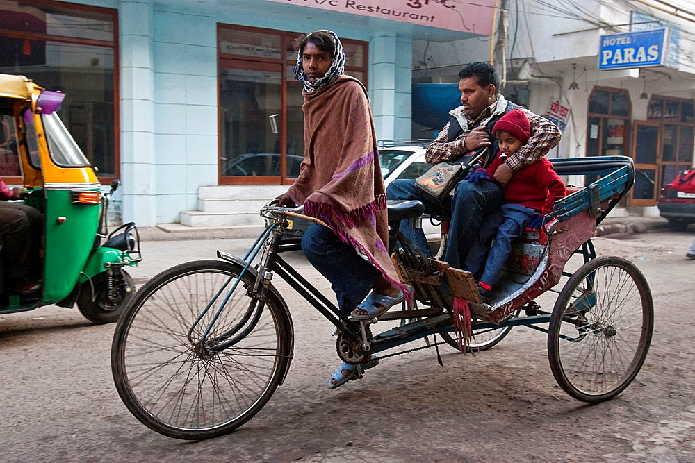 Father and Son travelling by Bicycle Taxi during the Morning Rush Hour, New Delhi, India