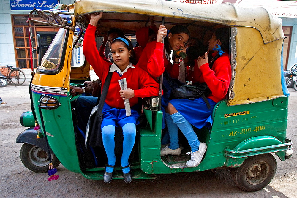 Children travelling to school by auto rickshaw during the morning rush hour, New Delhi, India