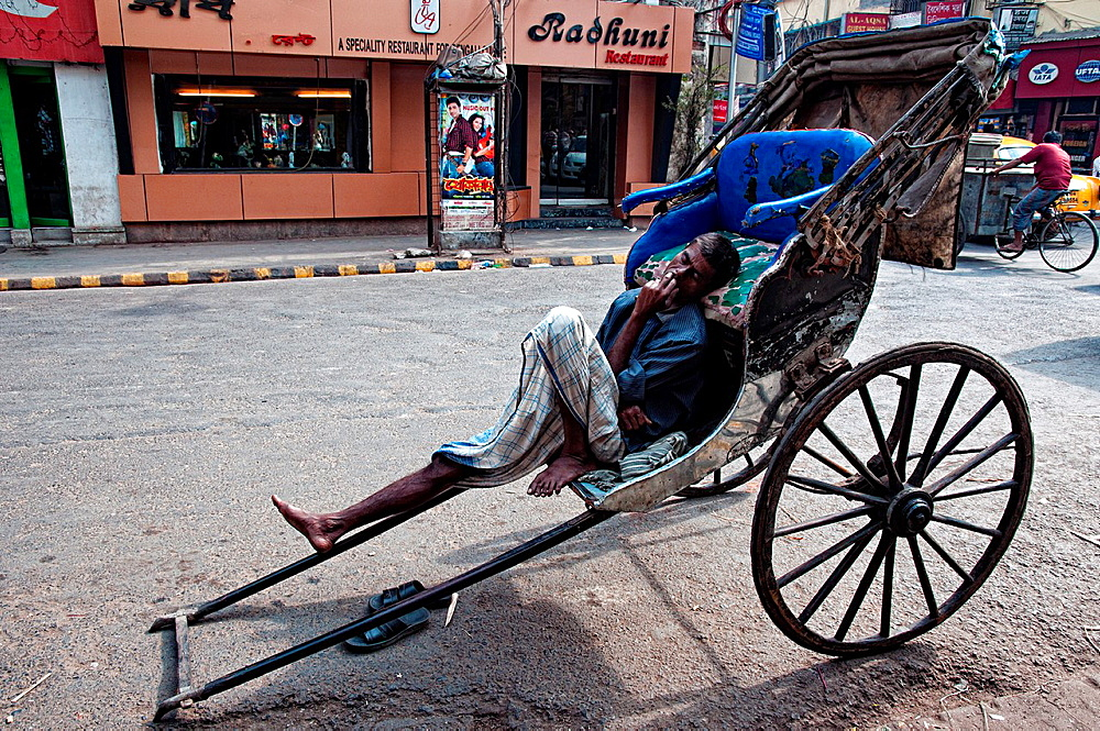 Rickshaw wallah sleeping on his rickshaw Calcutta, West Bengal, India