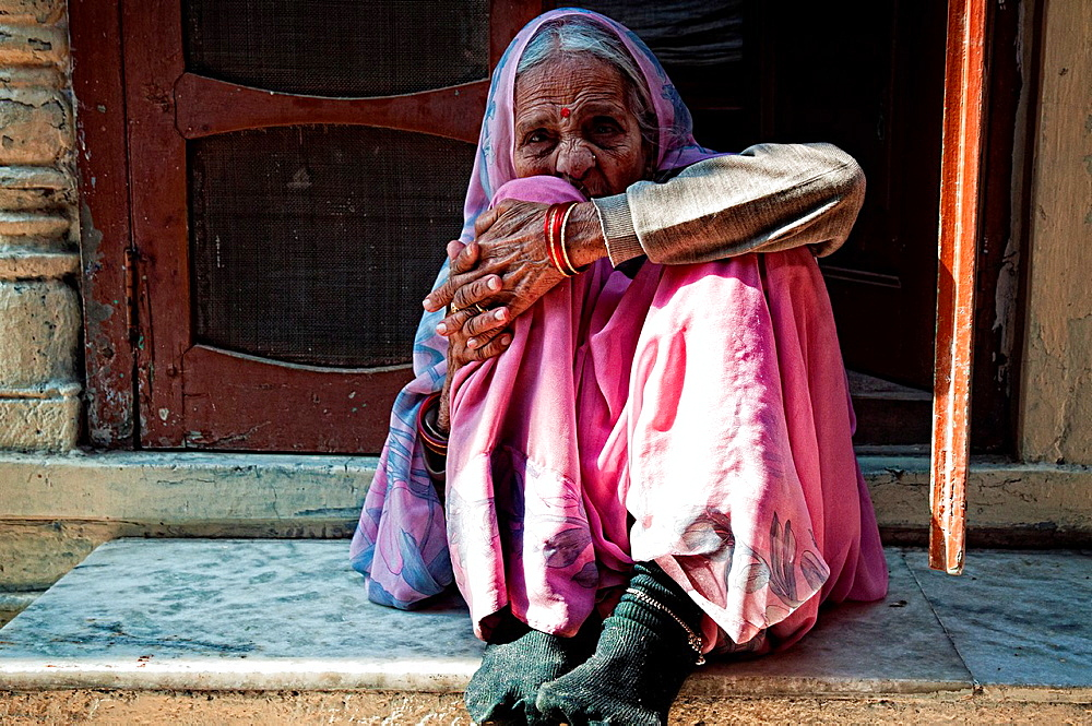 Portrait of an elderly woman wearing a pink sari and sitting at a doorway Jodhpur, Rajasthan, India
