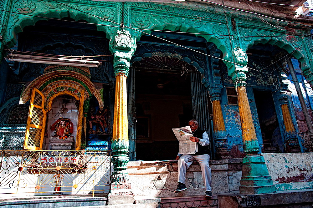 Man reading newspaper and sitting in front of a temple Jodhpur, Rajasthan, india