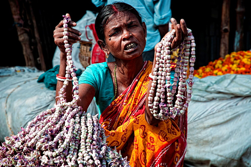 Woman selling flowers in Mullik ghat flower market Calcutta, West Bengal, India