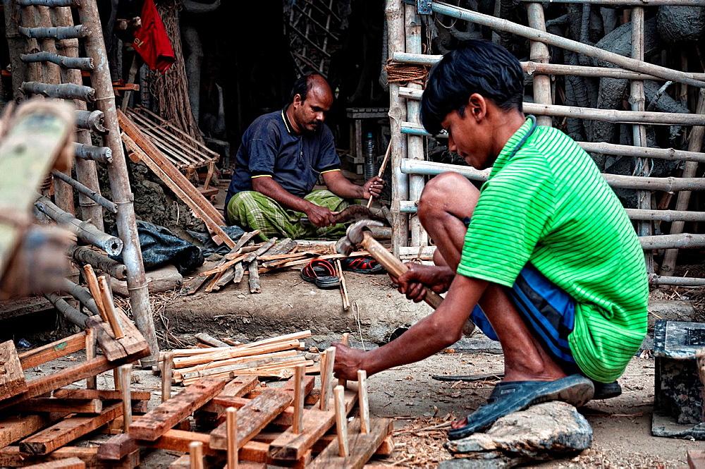 Men making effigies of gods in a workshop in Kumartuli district, Calcutta, West Bengal, India