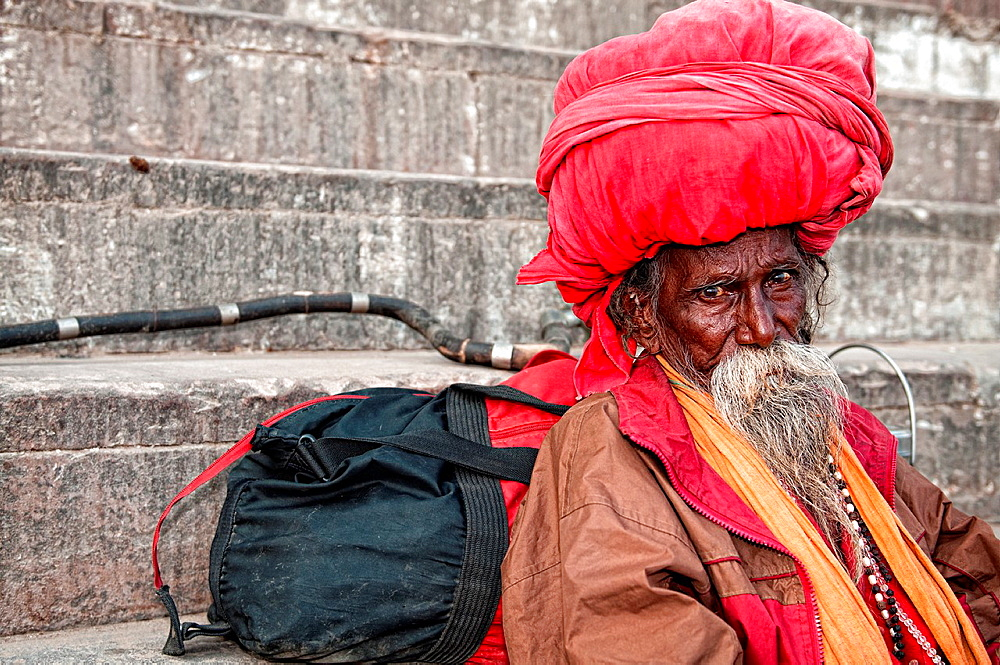 Sadhu wearing a big turban and sitting on the ghats. Varanasi, Benares, Uttar Pradesh, India