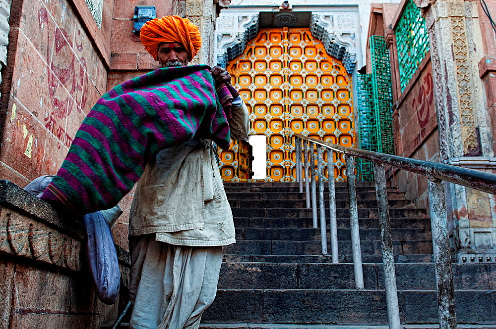 Man in traditional clothes at a temple entrace. Jodhpur, Rajasthan, India