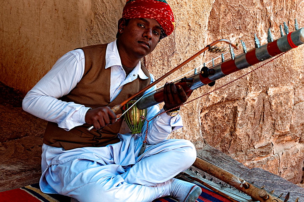 Portrait of a man playing a traditional musical instrument in Mehrangarh fort. Jodhpur, Rajasthan, India