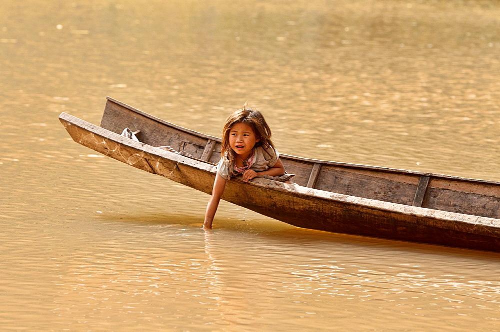 Lanten girl in her dugout canoe on the Nam Ha River, Luang Nam Tha, Laos