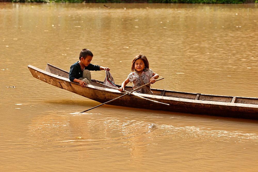 Lanten girl and boy in their dugout canoe on the Nam Ha River, Luang Nam Tha, Laos