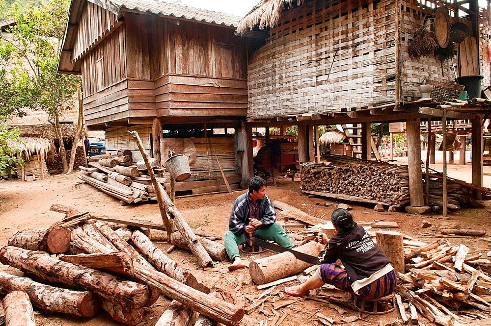 ethnic Khmu couple enjoying cutting wood, Luang Nam Tha, Laos