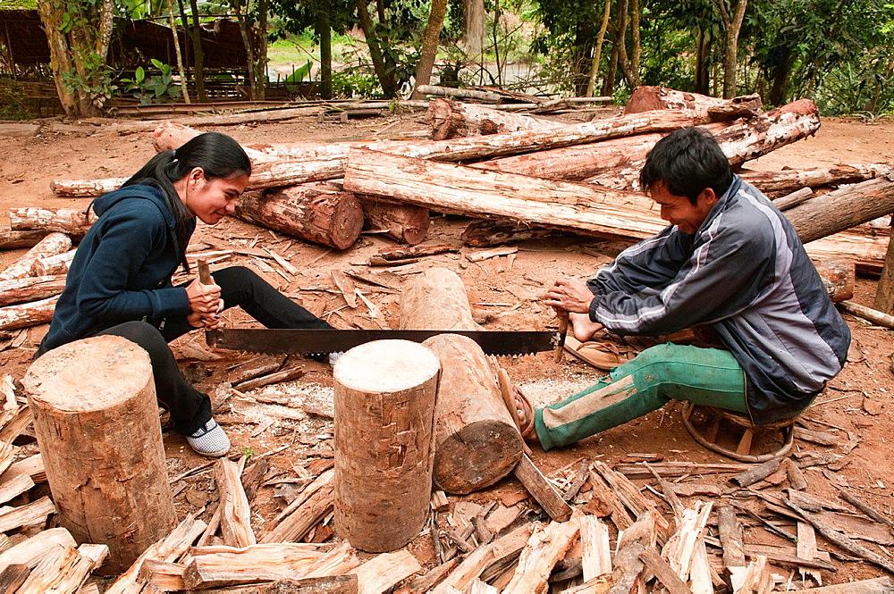 enjoying cutting wood, Luang Nam Tha, Laos