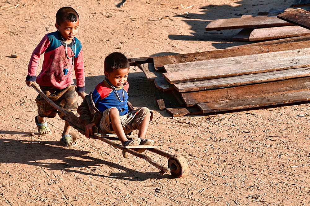 Akha boys playing with their homemade toy, Phongsaly, Laos