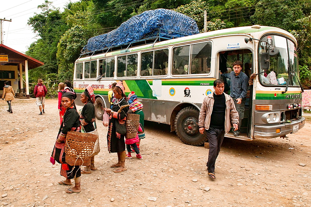 Akha women greeting a long distance bus enroute to Phongsaly, Laos