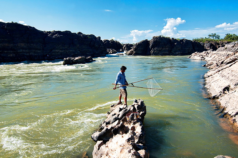 fisherman and his net in the Mekong River on Don Khone Island, Laos