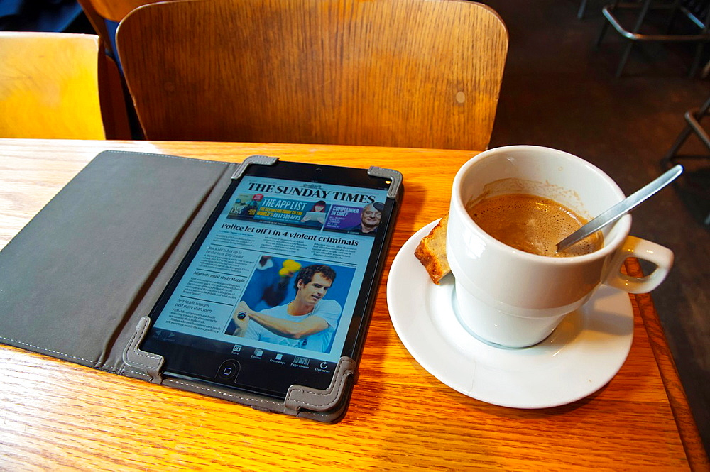 Cup of coffee and ipad mini with The Times newspaper Cafe Walvis in Dansaert district central Brussels Belgium Europe