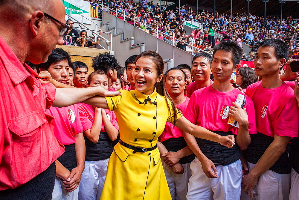 Chinese journalist jokes with man of Colla Vella Xiquets de Valls 'Castellers' building human tower, a Catalan tradition Biannual contest bullring Tarragona, catalonia,Spain