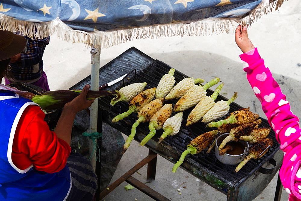 Ecuador, Salinas, vendor on the main square selling roasted corn.