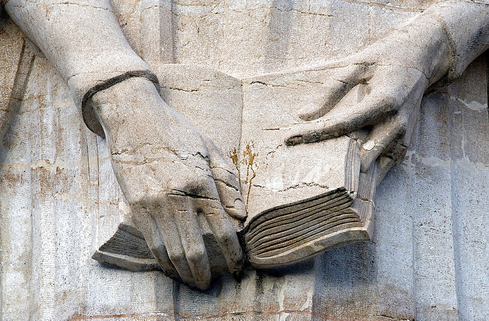 Jean Calvin Statue, close-up of his hands holding the bible, engraved in stone, Reformation Wall in Park des Bastions, Wall of Reformers, International reformation memorial in Geneva, Switzerland, Europe