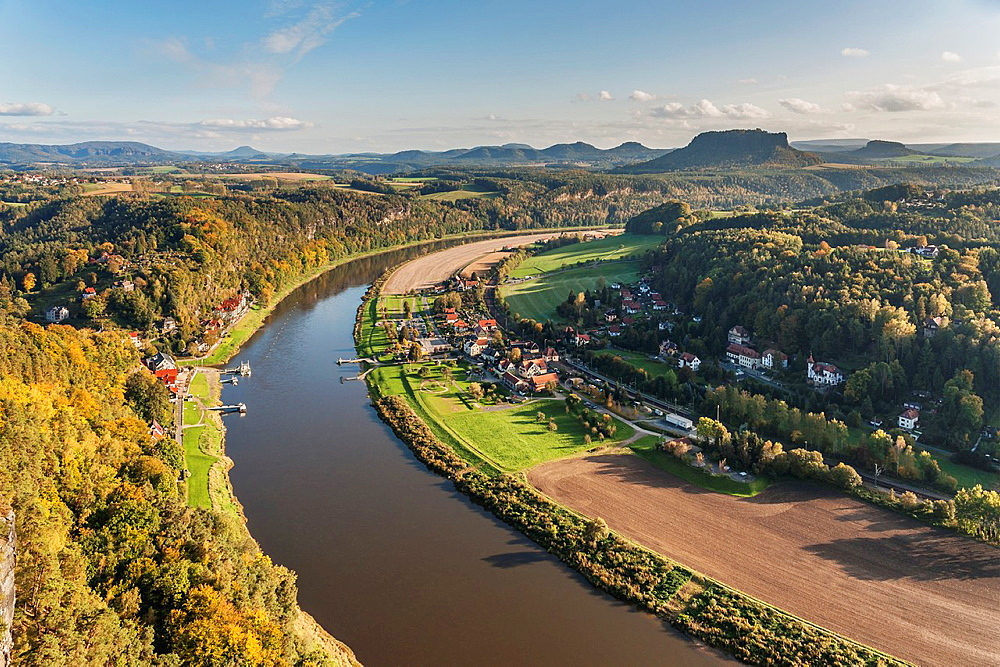 View from the spectacular rock formation Bastei Bastion in the national park Saxony Switzerland to the health resort Rathen near Dresden and to Elbe River. In the background is the Table Mountain Lilienstein. He is one of the most striking mountains in the Elbe Sandstone Mountains, Saxony, Germany, Europe