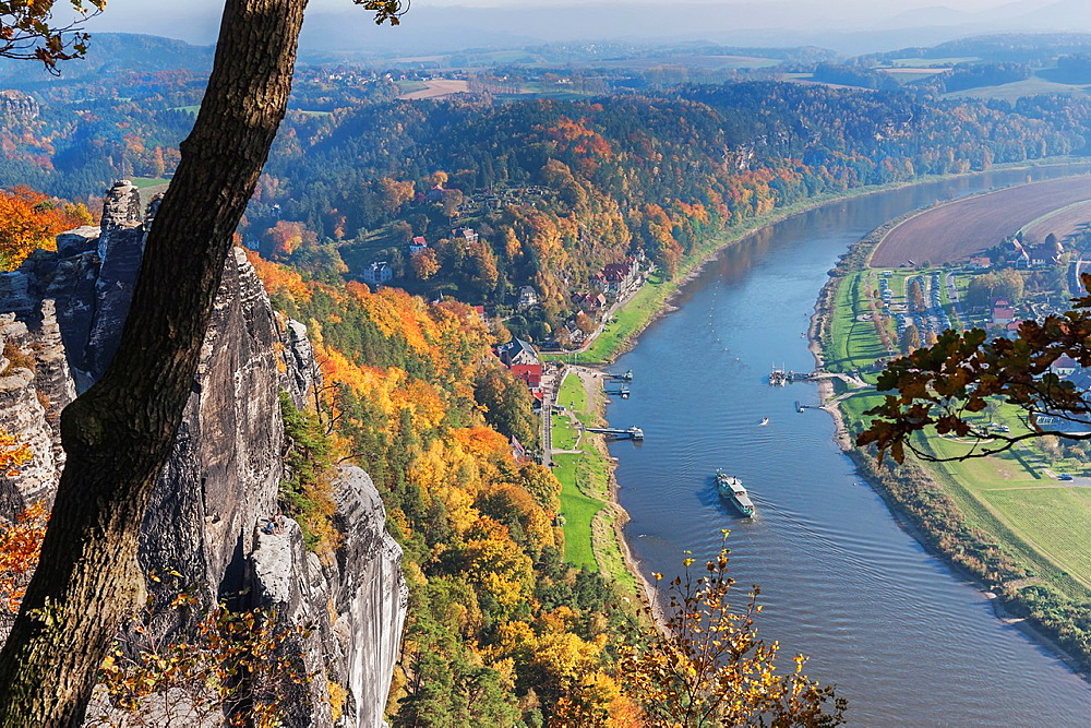 View from the spectacular rock formation Bastei Bastion to health resort Rathen and the Elbe River. The Bastei is one of the most visited tourist attractions in the national park Saxon Switzerland, municipality Lohmen, near Dresden, Saxony, Germany, Europe