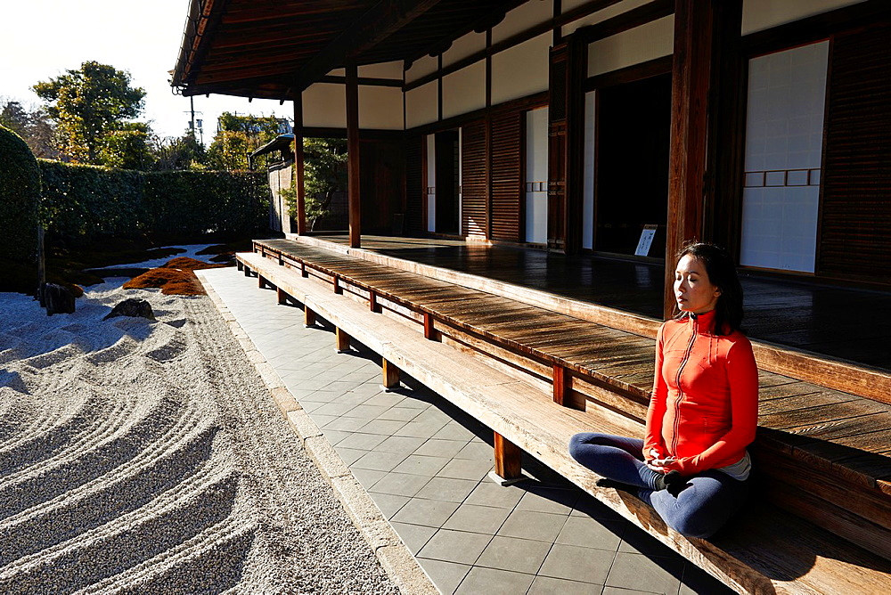 An asian woman meditates in the courtyard of the Garden of Solitary Sitting at the Zuiho-in, a sub-temple of the Daitokuji Monastery in Kyoto Japan