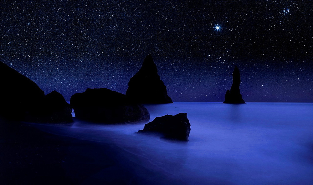 Starry night sky and Reynisdrangar cliffs, South Coast, Iceland digital composite