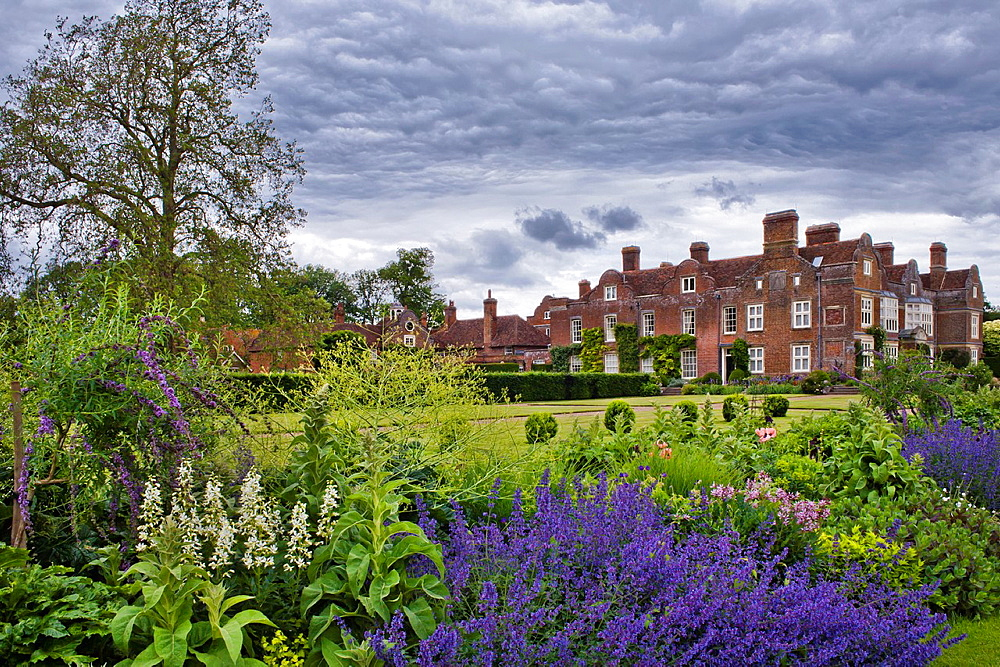 View of the garden across the herbaceous summer borders towards the house, Godinton House and Garden, Kent England.