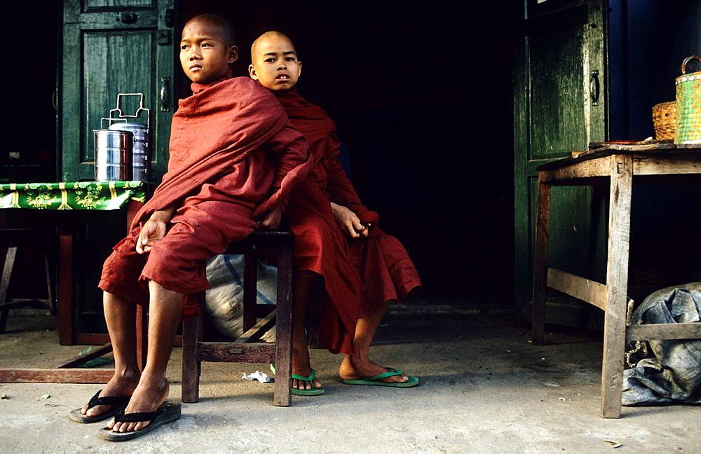 Two young Buddhist monks sit in front of a hut and wait
