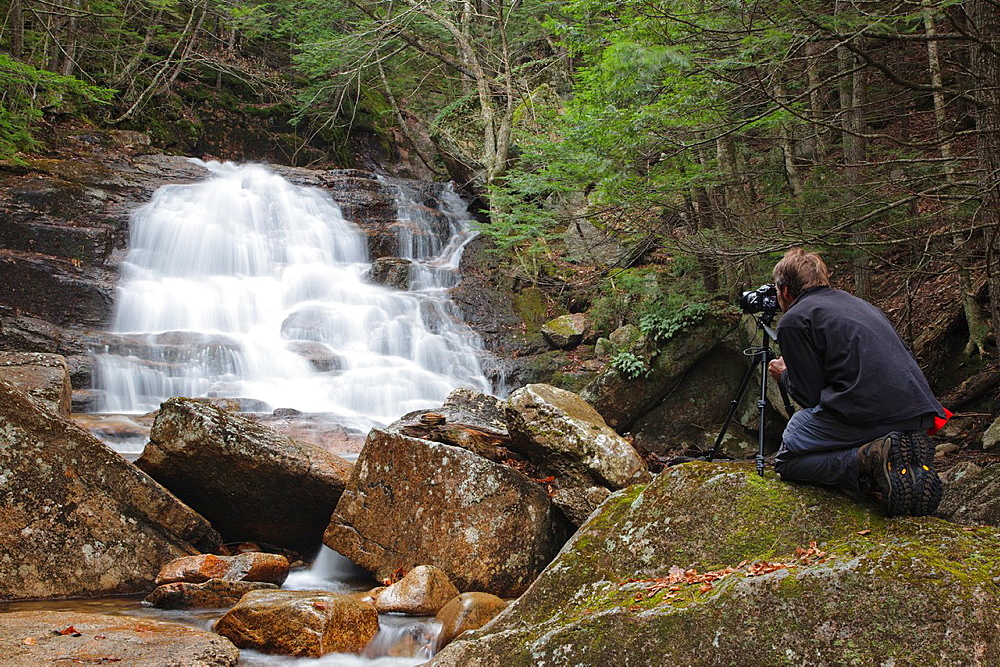 A photographer using a tripod at Ellen's Falls which are located along Hobbs Brook in Albany, New Hampshire USA.