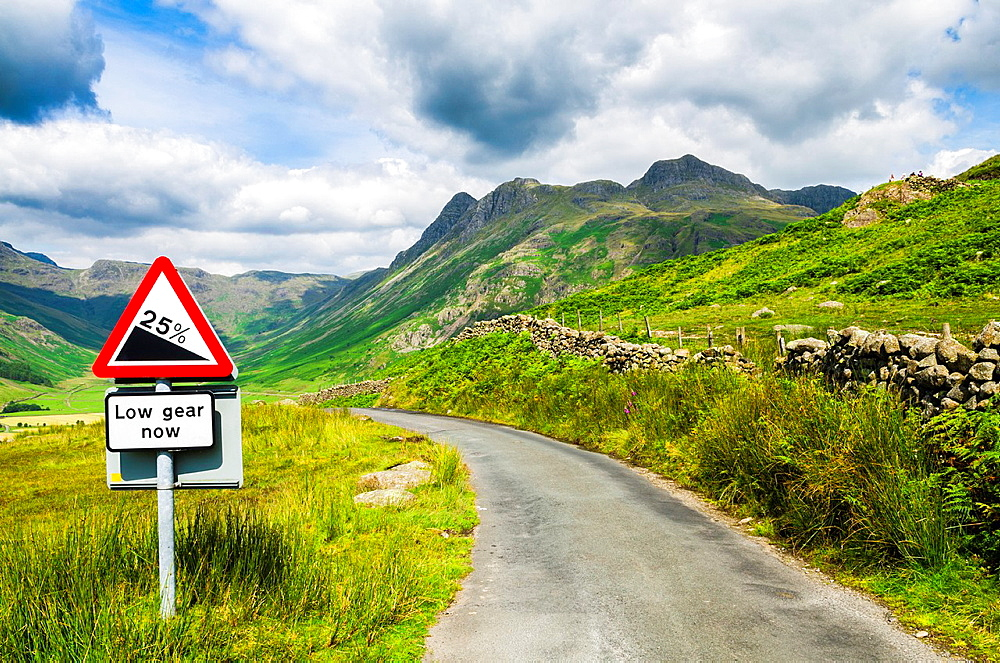 Steep hill warning sign on the roadside overlooking Langdale Fell in the Lake District, Cumbria, England.