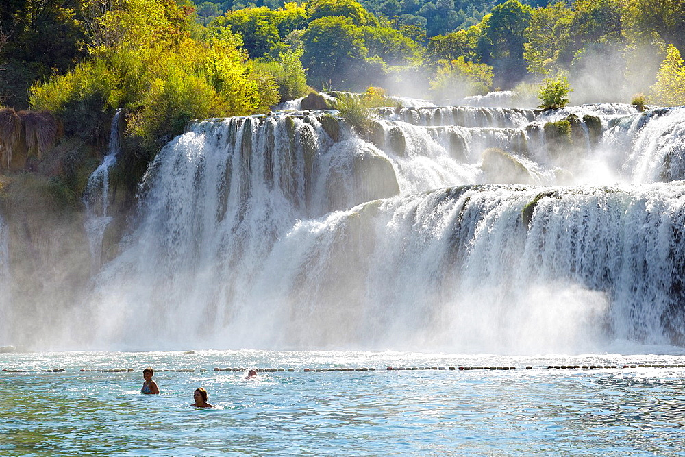 Croatia, Krka National Park, tourist taking bath near waterfall on the Krka River, Croatia.