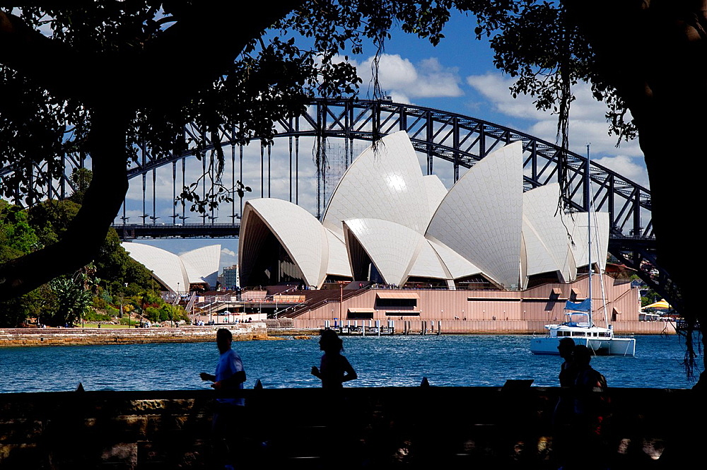 Silhouettes of morning walkers and joggers in front of the Sydney Opera House. Australia, New South Wales, Sydney.