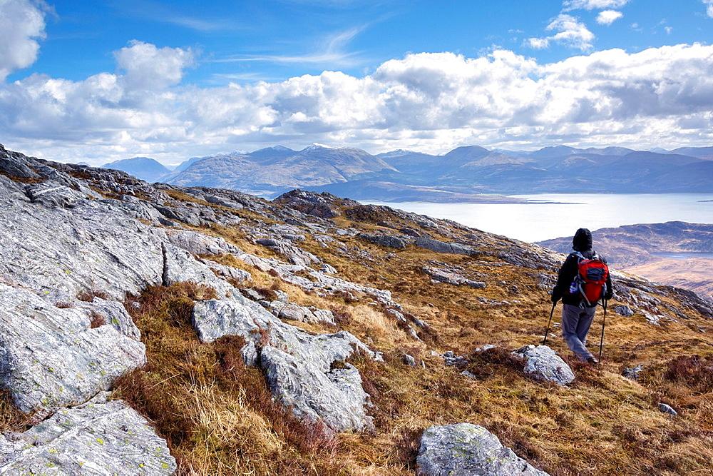 A hiker descending Sron a Garbh Choire Bhig in the Scottish Highlands.