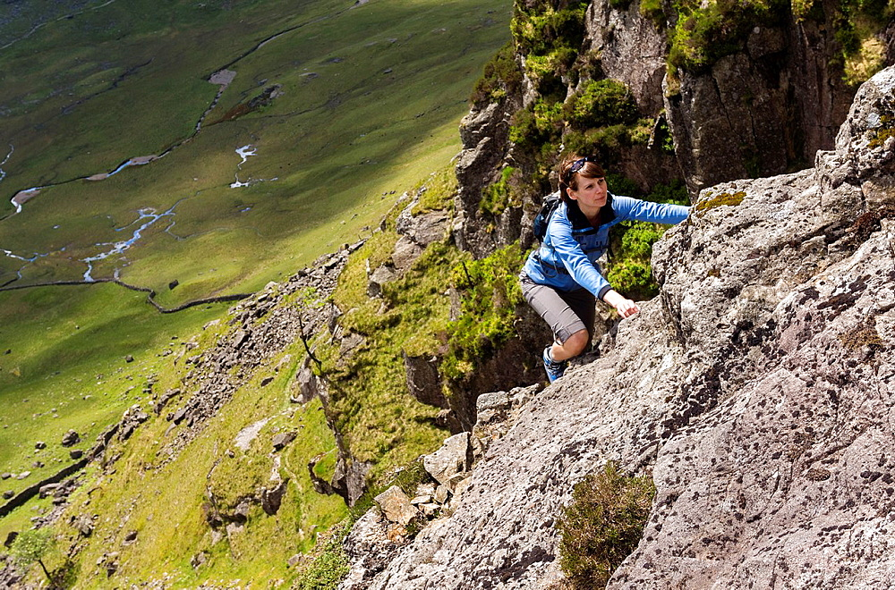 A rock scrambler on Gillercombe Crag (Rabbits Trod scramble) on Grey Knotts in the Lake District, UK.