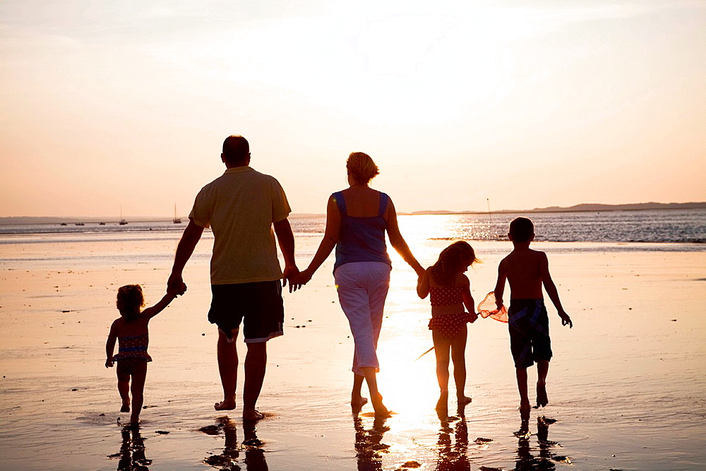 Family of five walking on beach at sunset