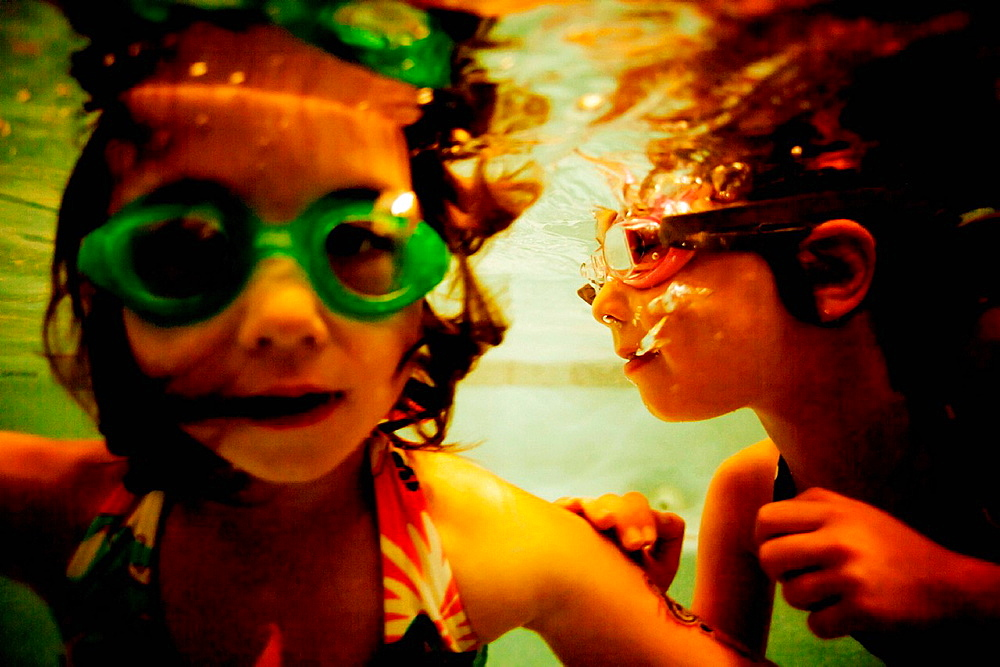 Two girls wearing goggles underwater, close up