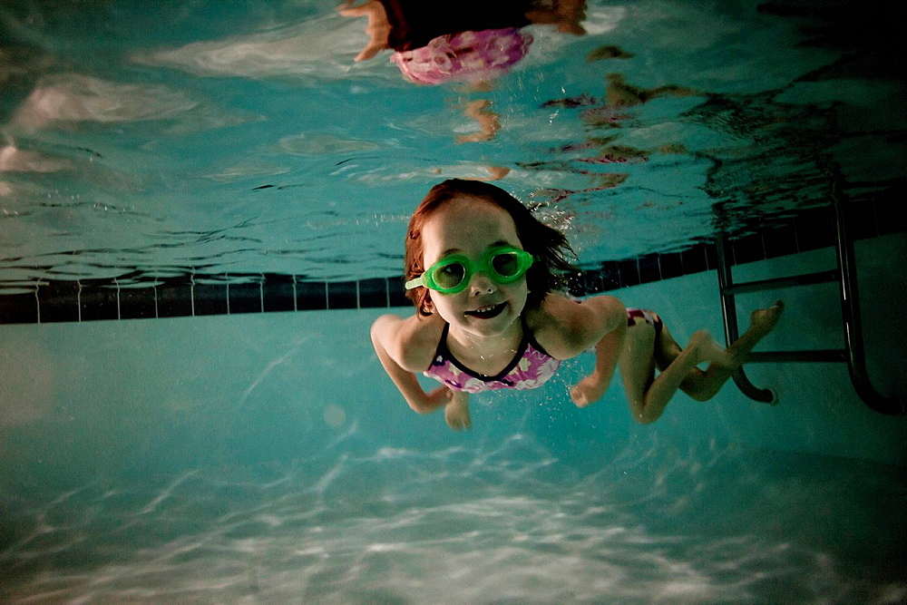 Girl wearing goggles swimming in pool, underwater view