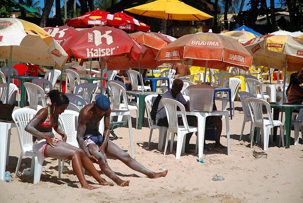 Salvador de Bahia, Bahia, Brazil, Praia de Itapoa, a couple putting peroxide on their legs to lighten hair