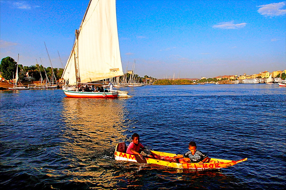 Felucca and kids' boat on the Nile river, at Aswan, Egypt