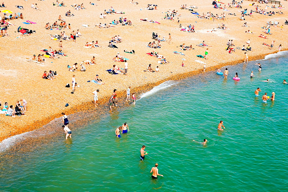 People on crowded beach, Brighton, England