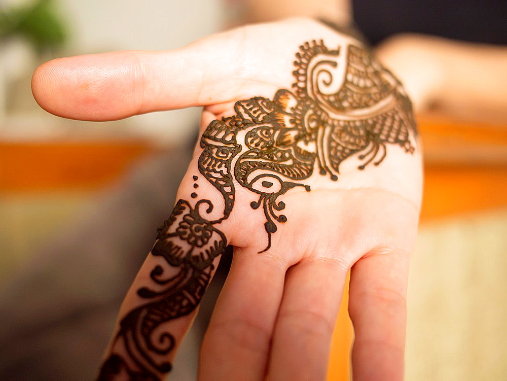 Fresh henna stains the palm of a young woman's hand in Bangalore, Karnataka, India.