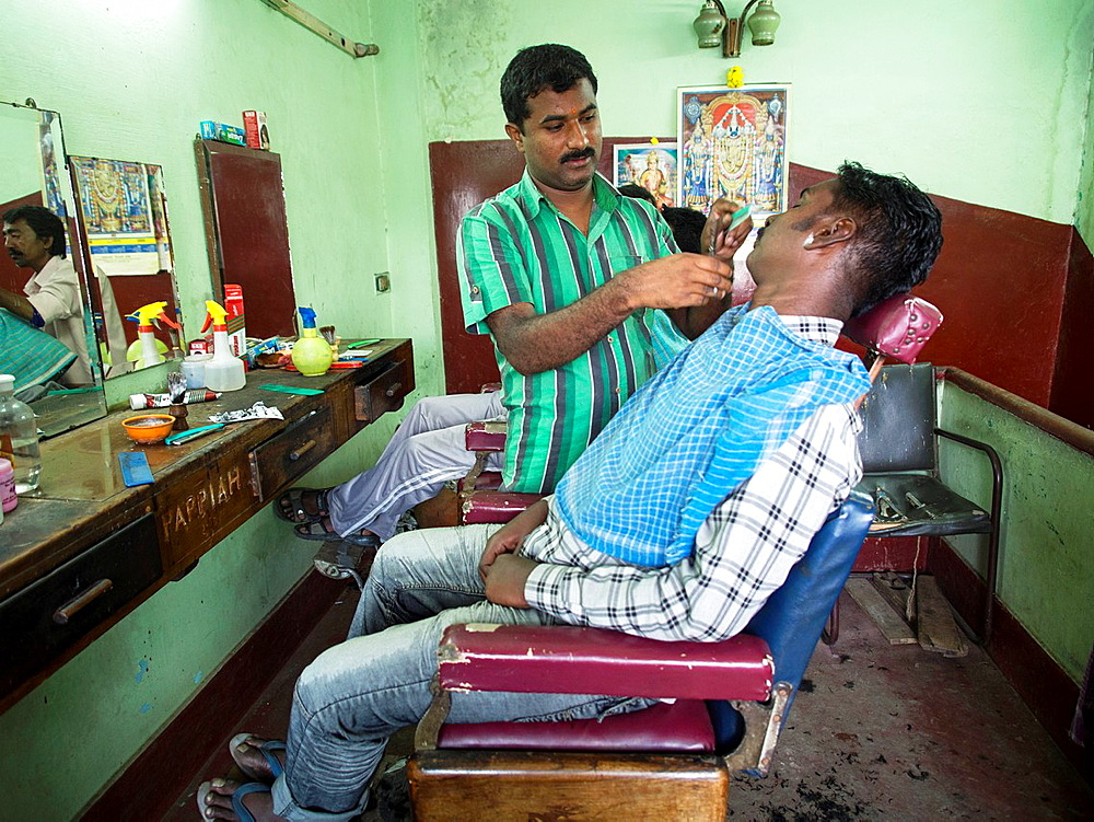 A man gets his beard shaved in a barbershop in Bangalore, Karnataka, India.