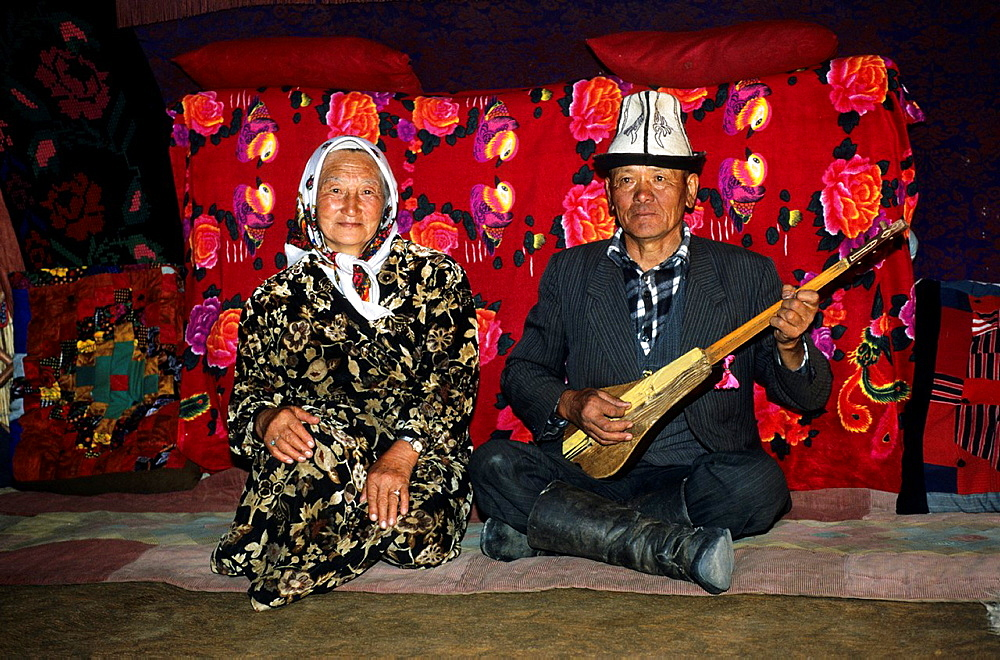 Kyrgyz Life, Nomad, a man is playing on a self made Guitar and his wife inside the Yourts, Traditional, Costume, Hat, Kyrgyzstan.
